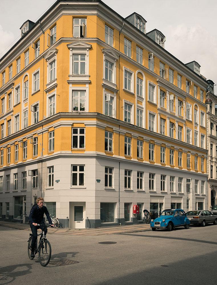 Person cycling through street, Nørrebro, Central Copenhagen, Denmark