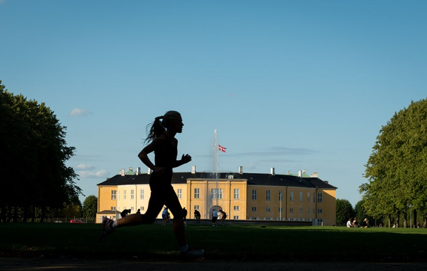 Woman running past Haerens Officersskole, Copenhagen, Denmark