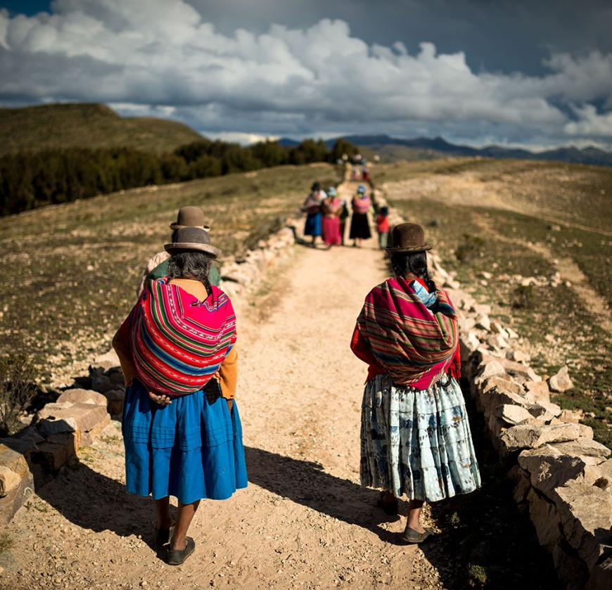 Bolivian women in traditional dress walking along The Inca Trail, Isla del Sol, Lake Titicaca, Bolivia