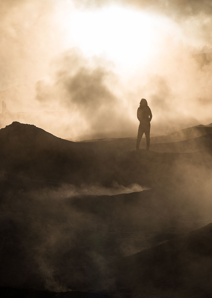 Figure standing amongst steam at the Sol de Mañana Geyser at dawn, Reserva Eduardo Avaroa, Bolivia
