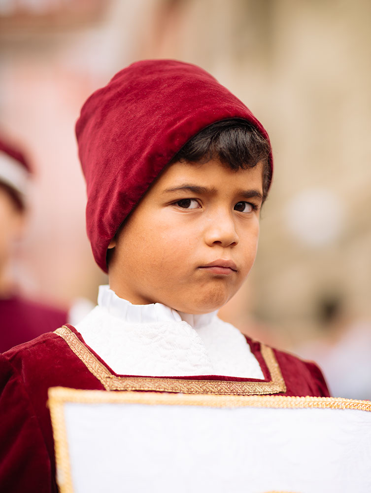Boy in Medieval costume parading through the streets of Asti