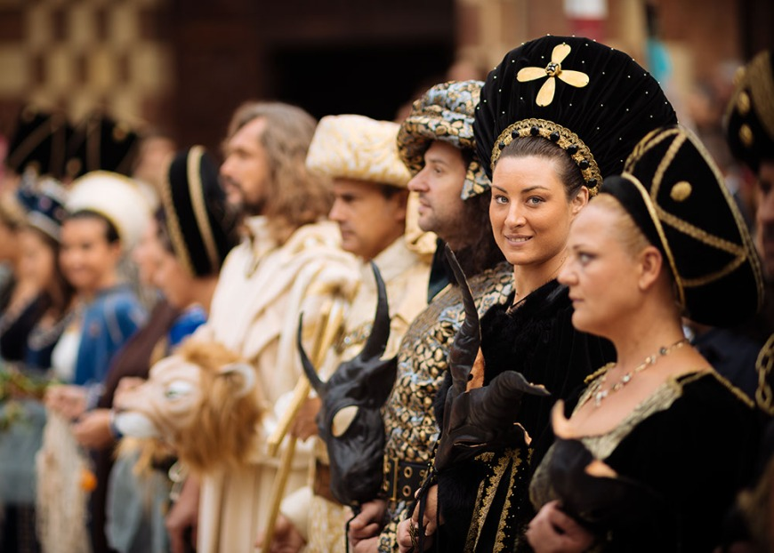 People dressed in traditional medieval costume gather in Piazza Cathedral for a blessing ahead of the Palio di Asti