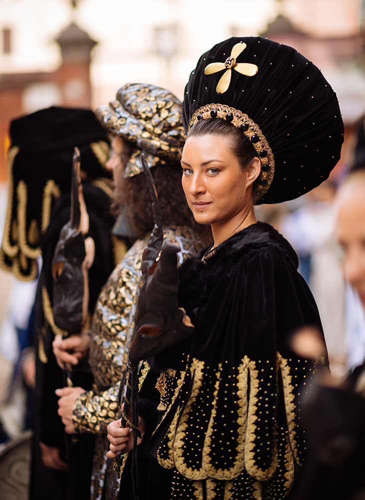 Portrait of young woman in traditional medieval costume ahead of the Palio di Asti