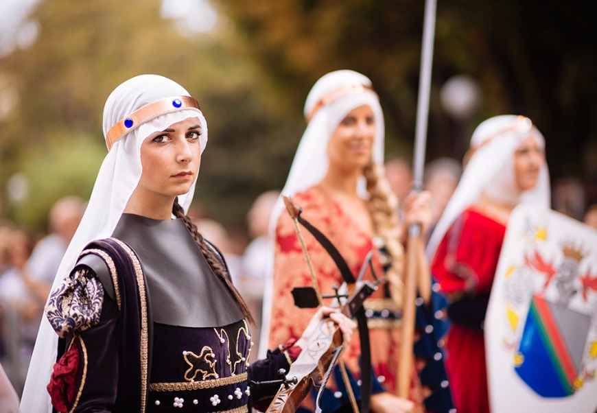 Women in a medieval costume takes part in a historical parade from the Piazza Cattedrale to the race track ahead of the Palio Di Asti on September 21, 2014 in Asti, Italy
