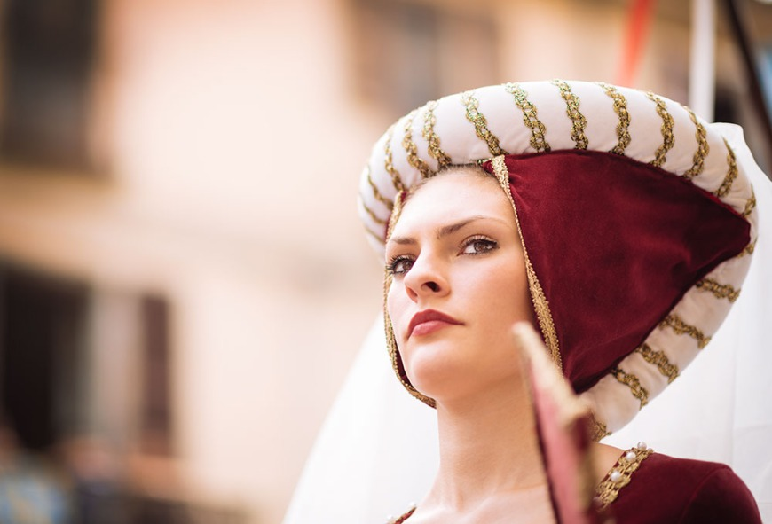 A woman in a medieval costume takes part in a historical parade from the Piazza Cattedrale to the race track ahead of the Palio Di Asti on September 21, 2014 in Asti, Italy