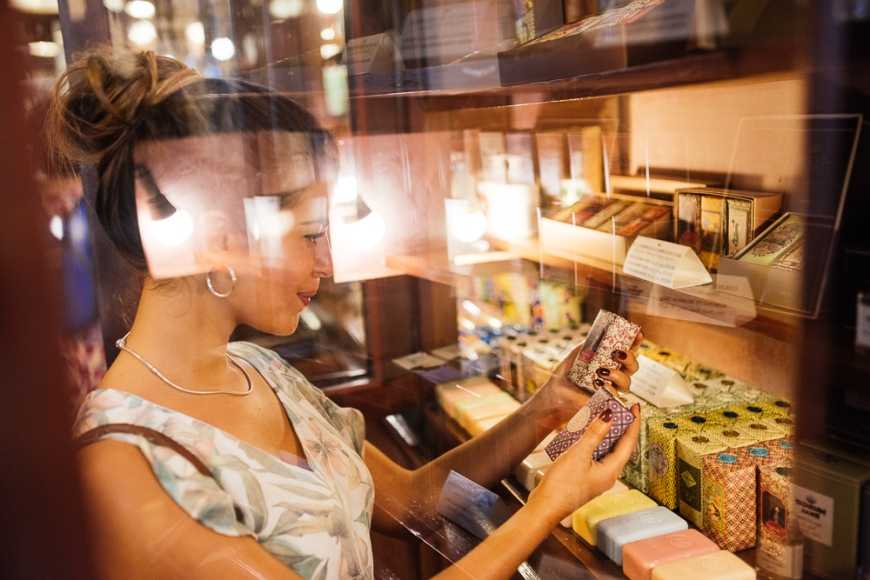 Young woman shopping for vintage Portugese products inside A Vida Portuguesa, Lisbon, Portugal