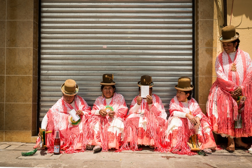 Dancers in traditional dress having a break, Fiesta de la Virgen de la Candelaria, Copacabana, Lake Titicaca, Bolivia