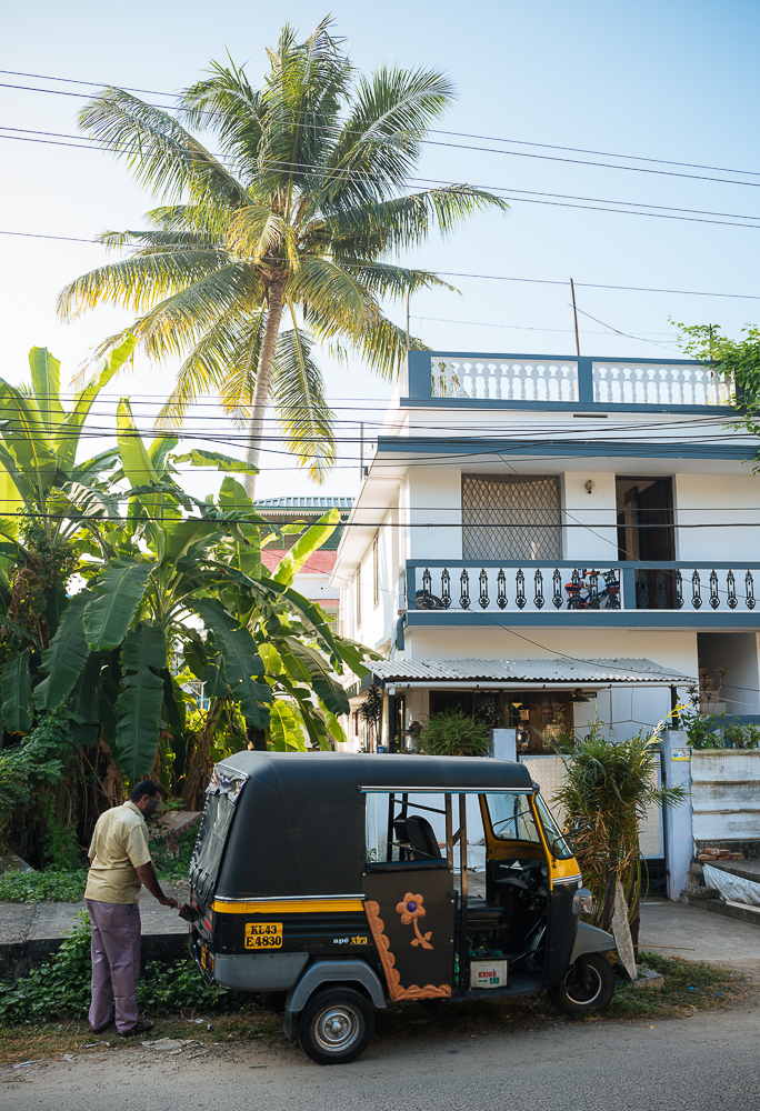 Man tending to parked rickshaw, Fort Kochi (Cochin), Kerala, India