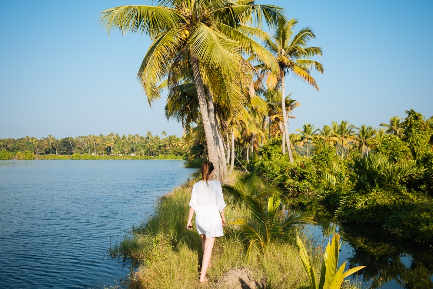 Young woman walking past palm trees, Backwaters near North Paravoor, Kerala, India