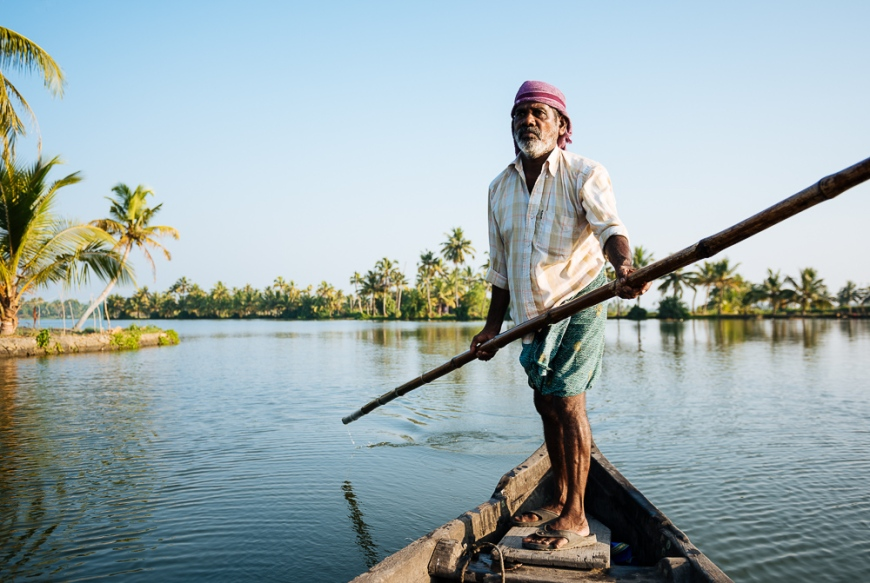 Anthony the boatman guiding the vessel through Keralan backwaters near North Paravoor, Kerala, India