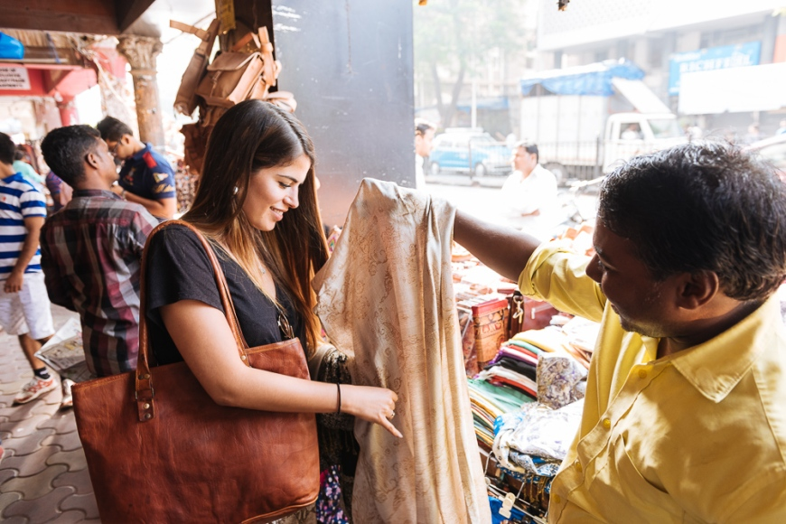 Young woman looking at textiles at street stall, Mumbai, India