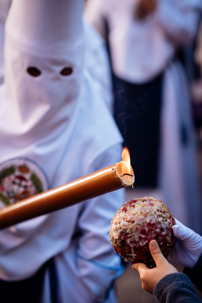A Penitent of 'Los Negritos' Brotherhood dripping candle wax onto a boy's wax ball during Semana Santa (Holy Week), Seville, Andalucia, Spain