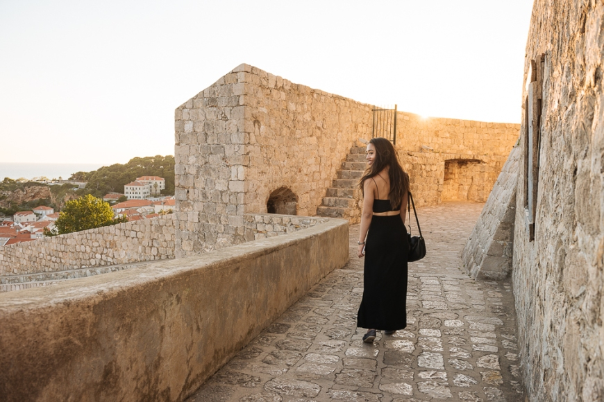 Young woman walking along City Walls, Dubrovnik, Croatia