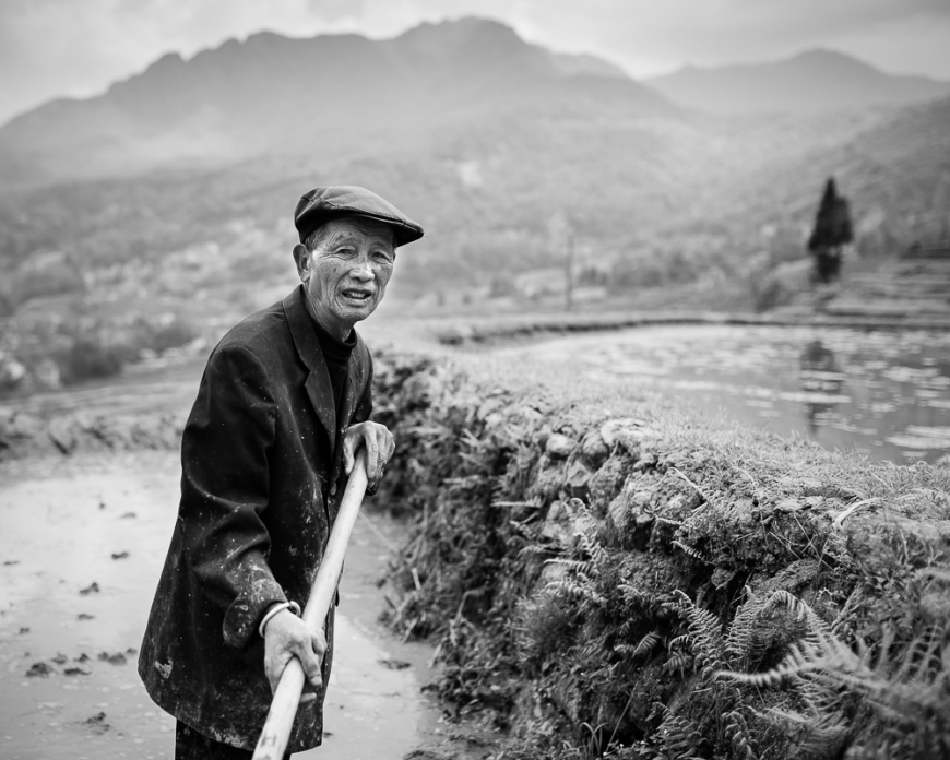 Farmer working in rice terrace, Duoyishu, Yuanyang, Yunnan Province, China