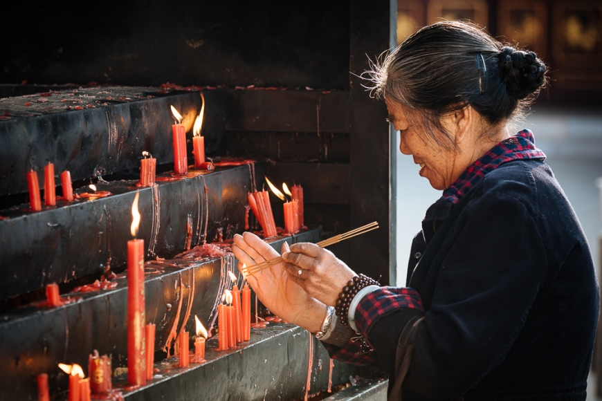 Woman lighting candles at Yuantong Buddhist Temple, Kunming, Yunnan Province, China