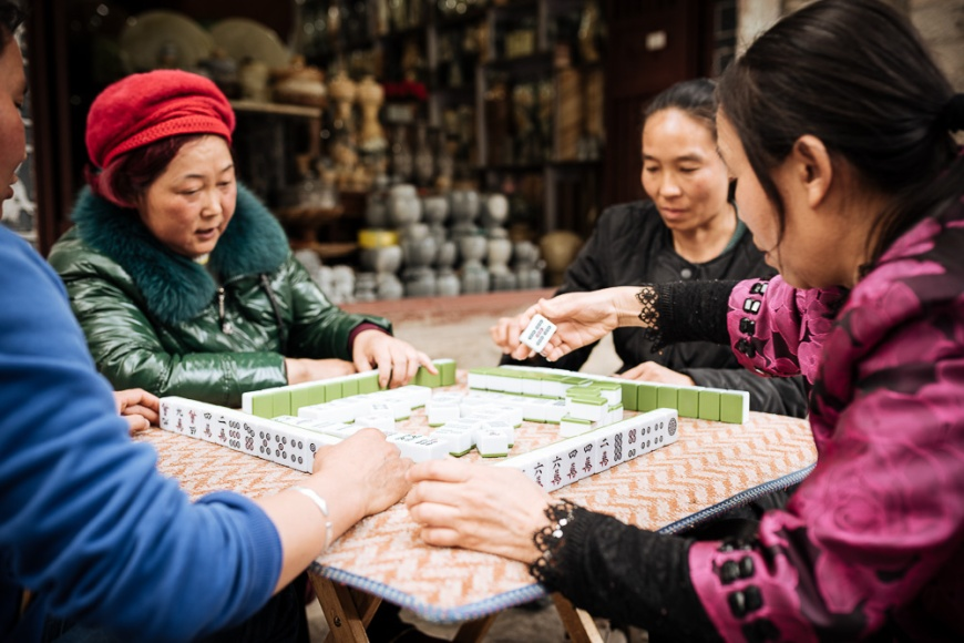 Women playing traditional Chinese game of Mahjong on street, Dali, Yunnan Province, China
