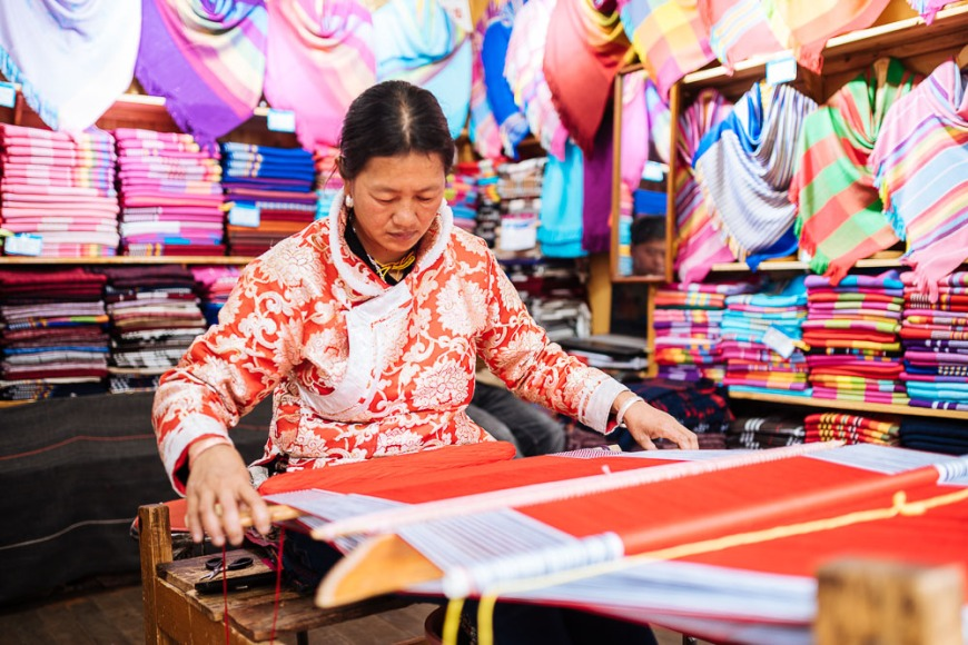Woman using traditional weaving machine, Lijiang, Yunnan Province, China