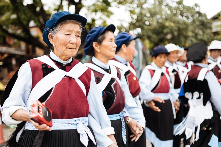 Naxi women in traditiona dress dancing, Lijiang, Yunnan Province, China