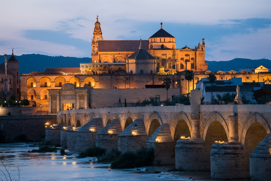 The Cathedral and former Great Mosque of Córdoba (Mezquita de Córdoba) and Roman Bridge (Puente Romano) over the Guadalquivir River at twilight, Cordoba, Andalucia, Spain