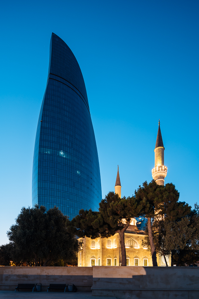 Exterior of The Shahid Mosque with Flame Towers in background at night, Baku, Azerbaijan