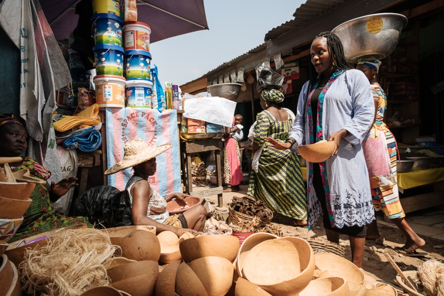 Woman choosing wooden bowl in Market, Accra, Ghana, Africa