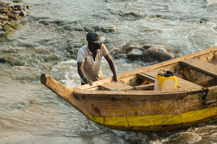 Fishermen pushing boat out to sea, Cape Coast, Ghana, Africa