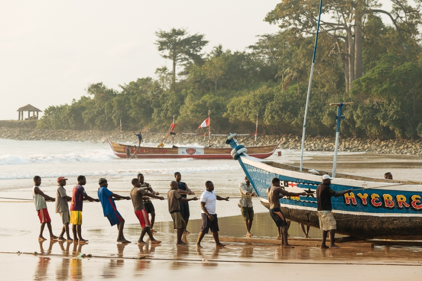 Men pulling boat out to sea, Busua, Ghana, Africa