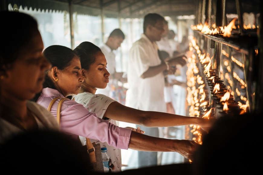People lighting candles, Temple of the Sacred Tooth Relic, Kandy, Central Province, Sri Lanka, Asia