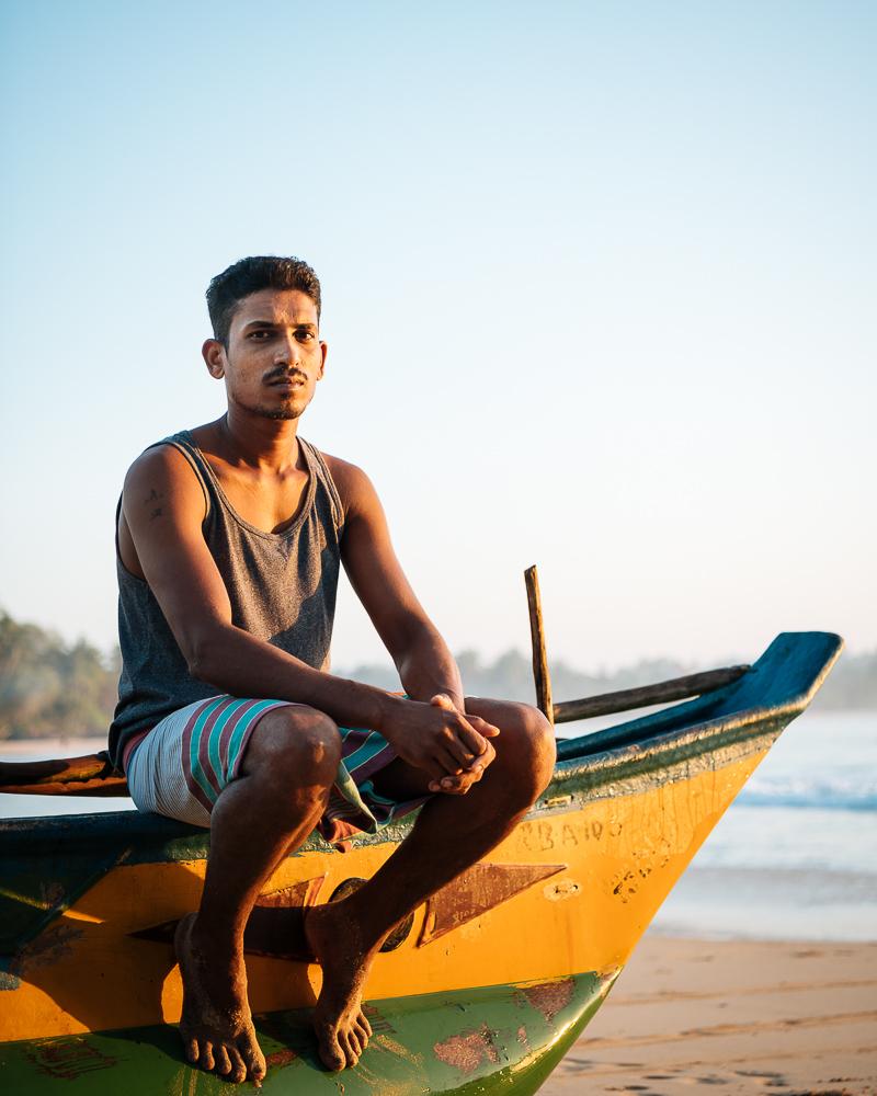 Portrait of fisherman Atljh sitting on his boat, Talalla Beach, South Coast, Sri Lanka, Asia